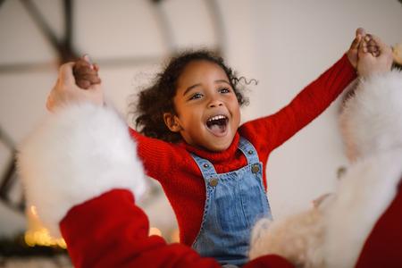 Foto de Santa Claus playing with cute african american Child at Home - Imagen libre de derechos