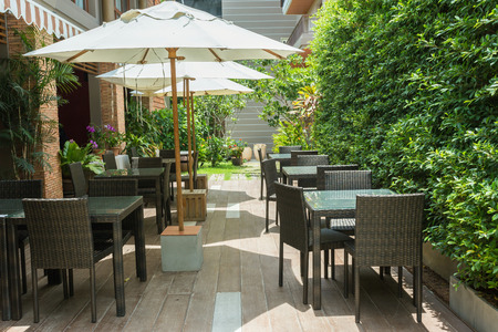 Photo for Cafe tables and chairs outside with big white umbrella and plant - Royalty Free Image