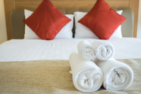 Photo for Close up of nice towels on white bed sheet with red pillow - Royalty Free Image