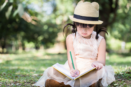 Foto de Little asian girl use pencil writting on notebook for writing book with smiling face in the park - Imagen libre de derechos