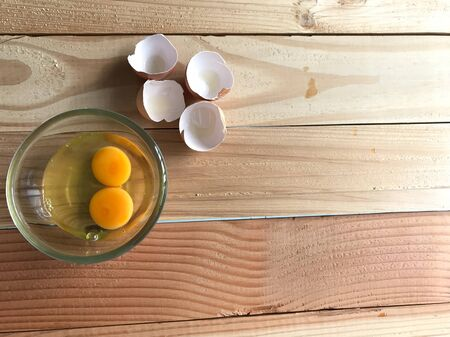 Photo for studio top view shot of two fresh yolk and egg white in clear glass cup and four eggshells beside it on natural rubber wood board with copy space on right side of frame - Royalty Free Image