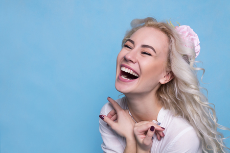 Foto de Beautiful young girl with flower in hair laughing. Copy Space - Imagen libre de derechos