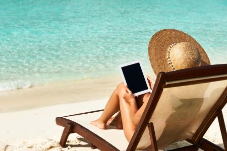 Foto de Young woman in hat with tablet pc at the beach - Imagen libre de derechos