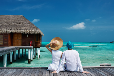 Foto de Couple on a tropical beach jetty at Maldives - Imagen libre de derechos