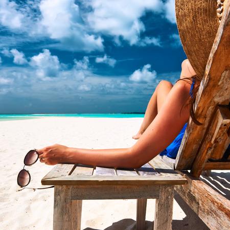 Photo pour Woman at beautiful beach holding sunglasses - image libre de droit