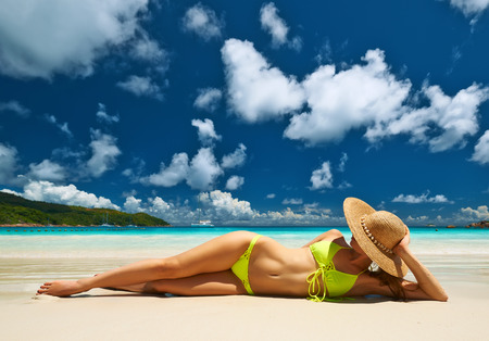 Photo for Woman in yellow bikini lying on tropical beach at Seychelles - Royalty Free Image