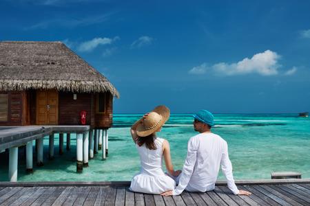 Photo pour Couple on a tropical beach jetty at Maldives - image libre de droit