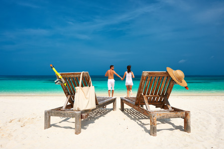 Photo for Couple in white running on a tropical beach at Maldives - Royalty Free Image