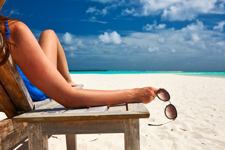Photo pour Woman at beautiful beach holding sunglasses - image libre de droit