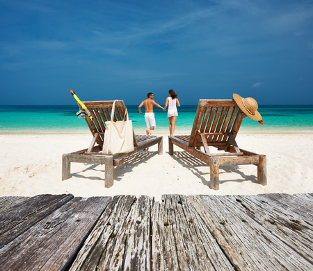 Foto de Couple in white relax on a tropical beach at Maldives - Imagen libre de derechos