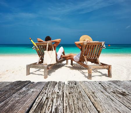 Foto de Couple in white relax on a tropical beach at Maldives - Imagen libre de derechos