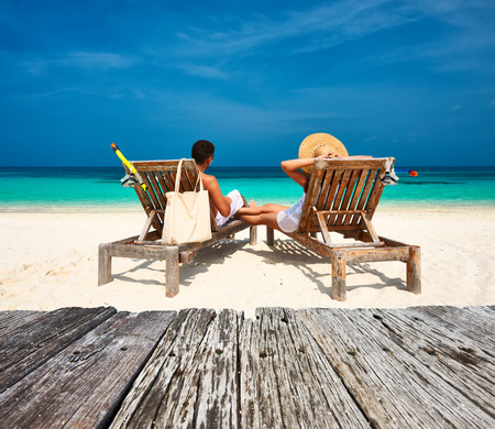 Photo for Couple in white relax on a tropical beach at Maldives - Royalty Free Image