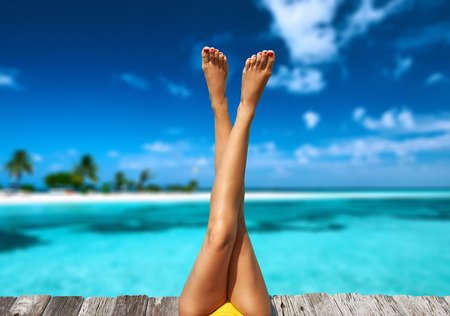 Photo pour Woman relaxing at beach jetty - image libre de droit