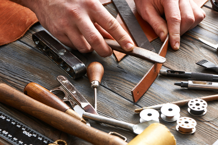 Photo for Man working with leather using crafting DIY tools - Royalty Free Image