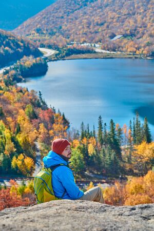 Foto de Backpacker man hiking at Artist's Bluff in autumn. View of Echo Lake. Fall colours in Franconia Notch State Park. White Mountain National Forest, New Hampshire, USA - Imagen libre de derechos