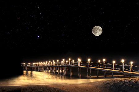 Photo pour Fantastic summer night with full moon and illuminated pier on beach. - image libre de droit