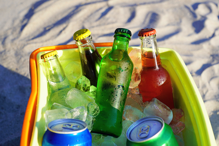 Foto de Soda drinks and filled ice cubes in a coolbox on the beach sand. - Imagen libre de derechos