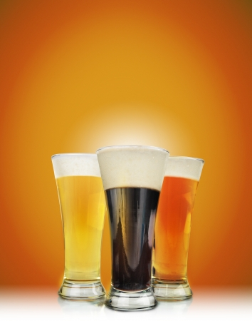 Three cold beer glasses have foam and are on a golden background