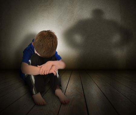 A young boy is sitting on the ground and scared with his face covered There is a shadow silhouette on the wall to represent abuse, fear, or a bully