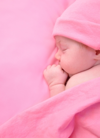 Photo for A newborn baby girl is sleeping on a pink blanket and is wearing a hat  Use it for a childhood, parenting or innocence theme  Add your text message to the side   - Royalty Free Image
