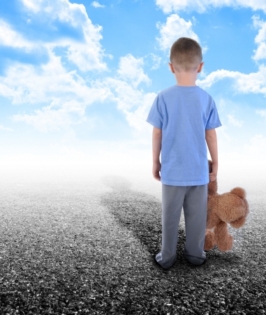 A young boy is holding a teddy bear and standing on an empty road with clouds in the sky