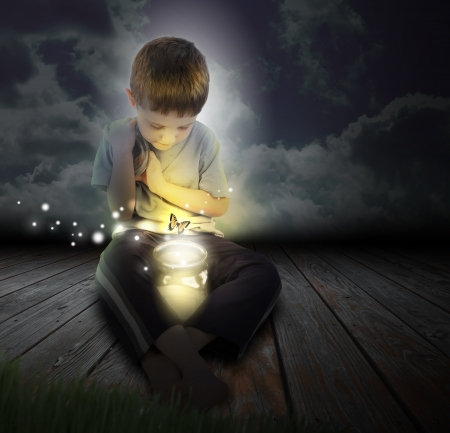 Photo for A boy is looking at a glowing bug firefly coming out of a jar with a butterfly at night - Royalty Free Image