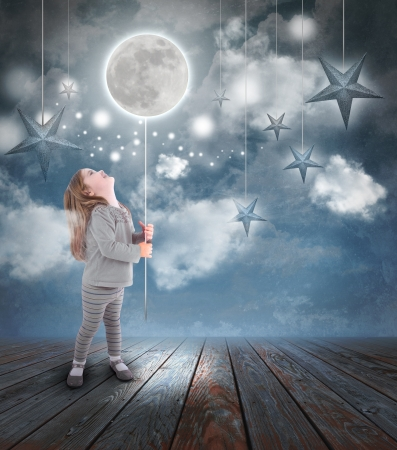 Photo for Young little girl playing at night with a balloon moon on a string with stars in the blue sky with clouds for a dream concept. - Royalty Free Image