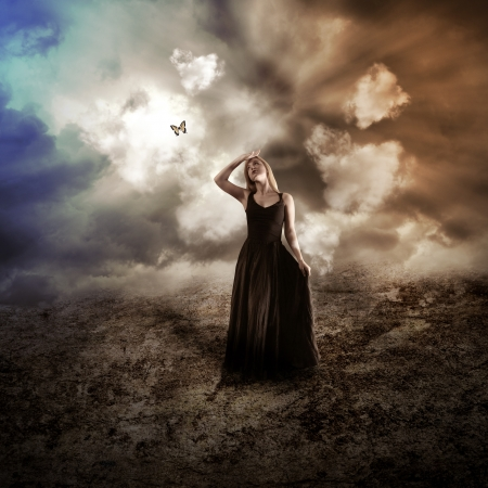 Foto de A young woman is wearing a black dress in a dark dry, nature landscape with a butterfly flying up to represent hope  - Imagen libre de derechos