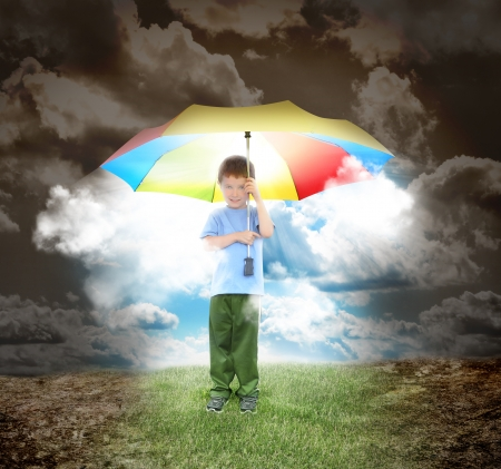 Foto de A young child is holding a rainbow umbrella with sunshine glowing out  The boy is surrounded with a dried up landcsape and grass under his shoes for a home concept  - Imagen libre de derechos