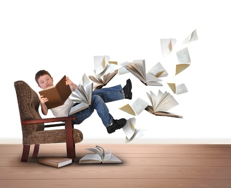 Foto de A young boy is reading a book floating in in the air on a white isolated background. There are pieces of paper flying up around him for an education concept.  - Imagen libre de derechos