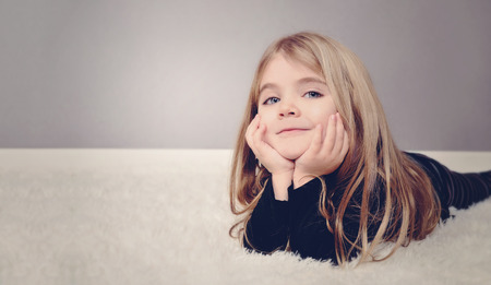 Photo for A happy little girl is laying on the white floor with copyspace area for a text message  Use it for a home or family concept  - Royalty Free Image