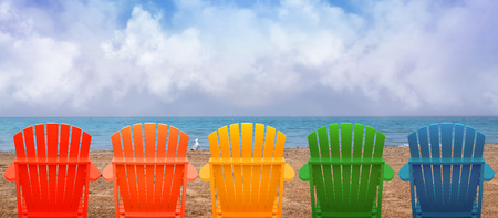 Foto de A rainbow of colors of wooden beach chairs are lined up along the water shore. - Imagen libre de derechos