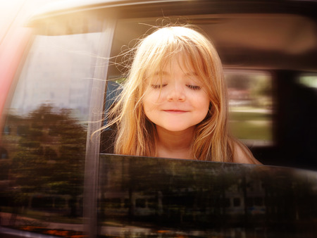 Photo pour A little girl is sticking her head out the car window and looking down for a road trip or travel concept  - image libre de droit