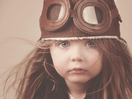 Foto de A little girl is wearing a pilot hat with goggles with an antique concept for carrer or imagination message  - Imagen libre de derechos