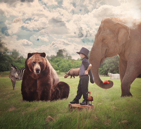 Photo pour A brave child is standing in a nature field with wild animals around him such as a bear, elephant, zebra and bear for an imagination or creative concept  - image libre de droit
