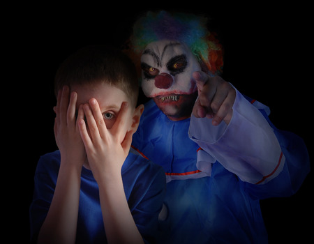 Photo for A child is hiding his eyes in the dark night and looks scared and upset at creepy clown  The boy is isolated on a black background for a fear concept  - Royalty Free Image