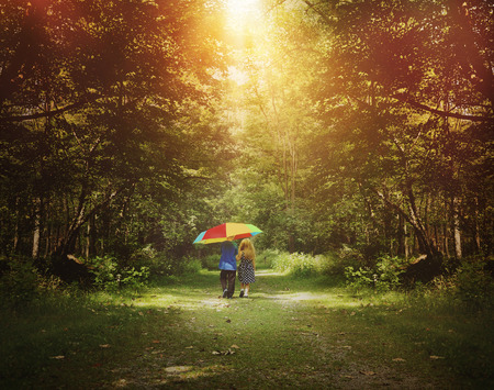 Photo for Two children are walking down a sunshine trail in the woods holding a rainbow umbrella for a friendship, hope or happiness concept  - Royalty Free Image