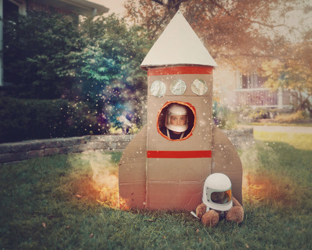 Foto de A young boy is sitting in a cardboard space rocket ship with an astronaut helmet on. He is in the front yard imagining he is in space with stars. - Imagen libre de derechos