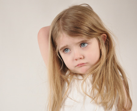 Foto de A little child looks sad and frustrated. The girl has her hand over her head for a parenting or tired concept. - Imagen libre de derechos