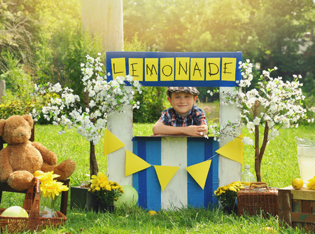 Photo pour A little boy has an outdoor  homemade lemonade stand with a sign and he looks happy for a small business or money concept. - image libre de droit