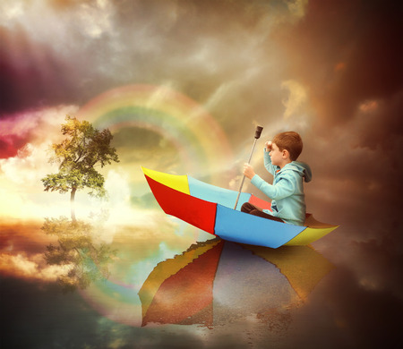 Foto de A little child is sitting in an umbrella boat looking at a distant tree of light with a rainbow for an imagination or freedom concept. - Imagen libre de derechos