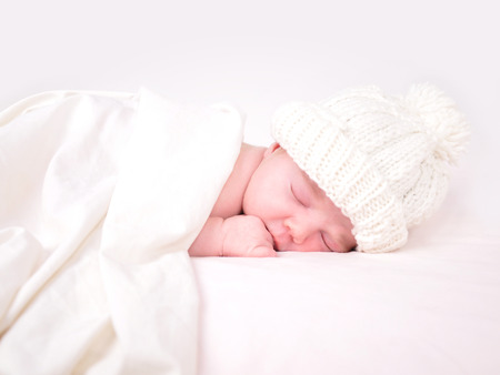 Photo pour A young baby is sleeping on a white bed with a blanket. - image libre de droit