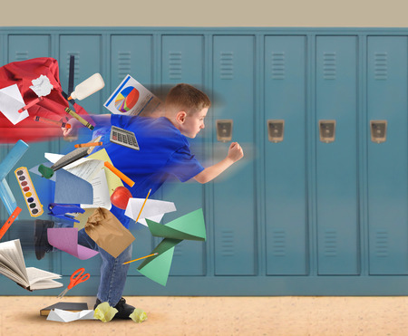 Foto de A school boy is running late with school supplies falling out of his book bag in a hallway with lockers in the background for an education or academic concept. - Imagen libre de derechos