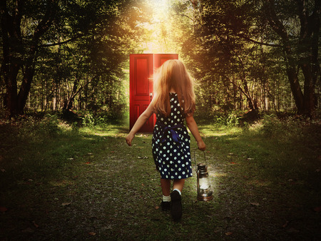 Photo pour A little child is walking in the woods holding a light and looking at a glowing red door on the path for a mystery or imagination concept. - image libre de droit