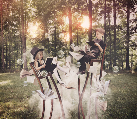 Foto de Two children are reading books on long, surreal chairs in the woods with smoke underneath with bubbles in the air for an education or imagination concept. - Imagen libre de derechos