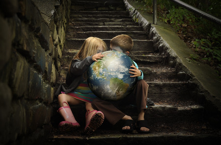 Foto de Children are holding the planet earth on wet dark stairs for a weather or season concept about the enviornment. - Imagen libre de derechos