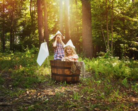 Foto de A little boy and girl are pretending to fish in a wooden barrel boat in the nature woods with a real fish being caught by the children for an imagination or creativity concept. - Imagen libre de derechos