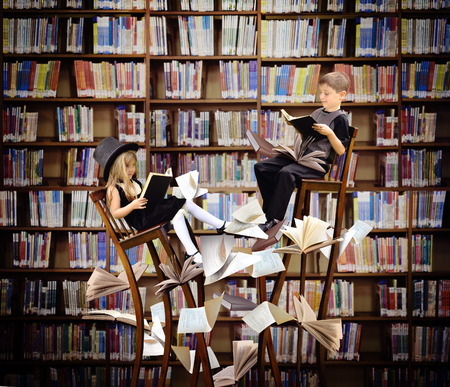 Foto de Two children are reading books on long, surreal wooden chairs in a library with books and papers flying around them for an education or imagination concept. - Imagen libre de derechos