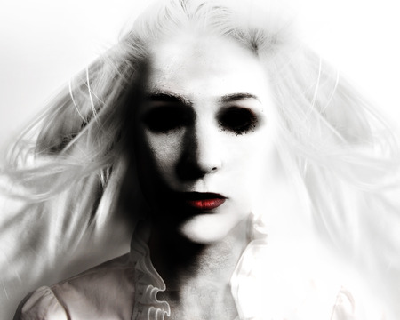 Photo for A scary evil woman with black eyes and red lips is death on a white background for a fear or Halloween concept. - Royalty Free Image