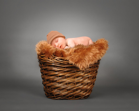 Foto de A cute little baby is sleeping in a wooden basket with brown fur and is wearing a hat. The baby could be a boy or girl on a isolated gray photography backdrop for a parenting or love concept. - Imagen libre de derechos